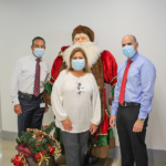A woman and two men posing in front of a santa clause