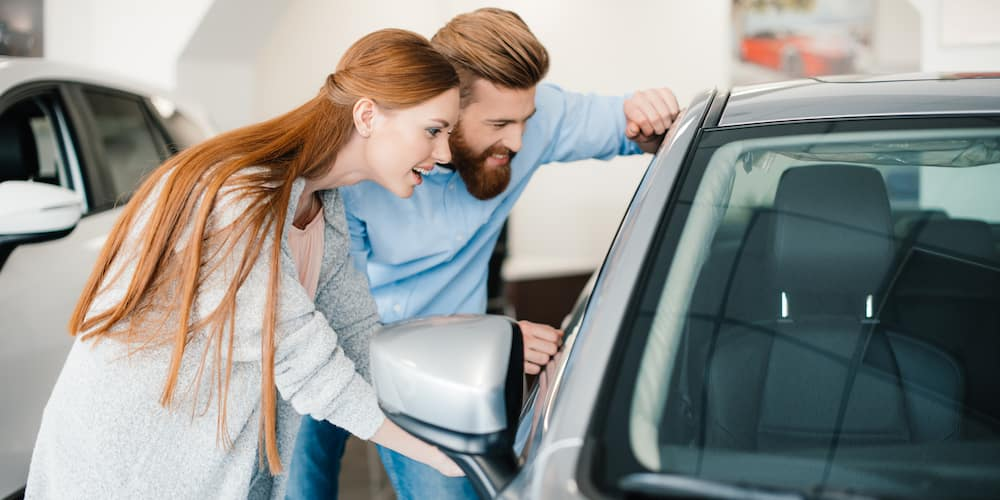 Young Couple Looking at Car