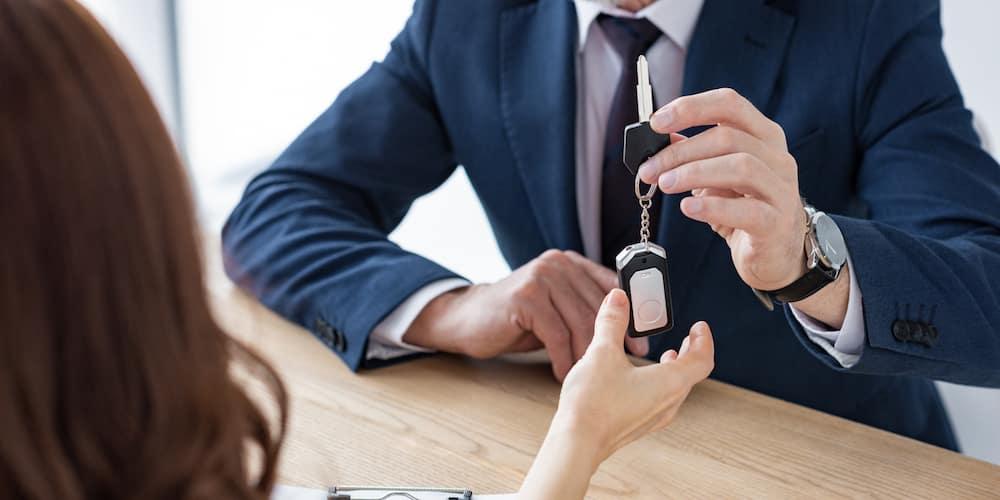 Car Dealer Handing Woman Key
