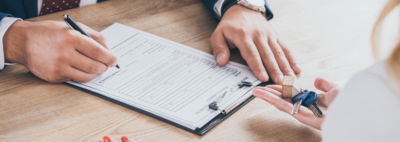Man Signing Document at Dealership