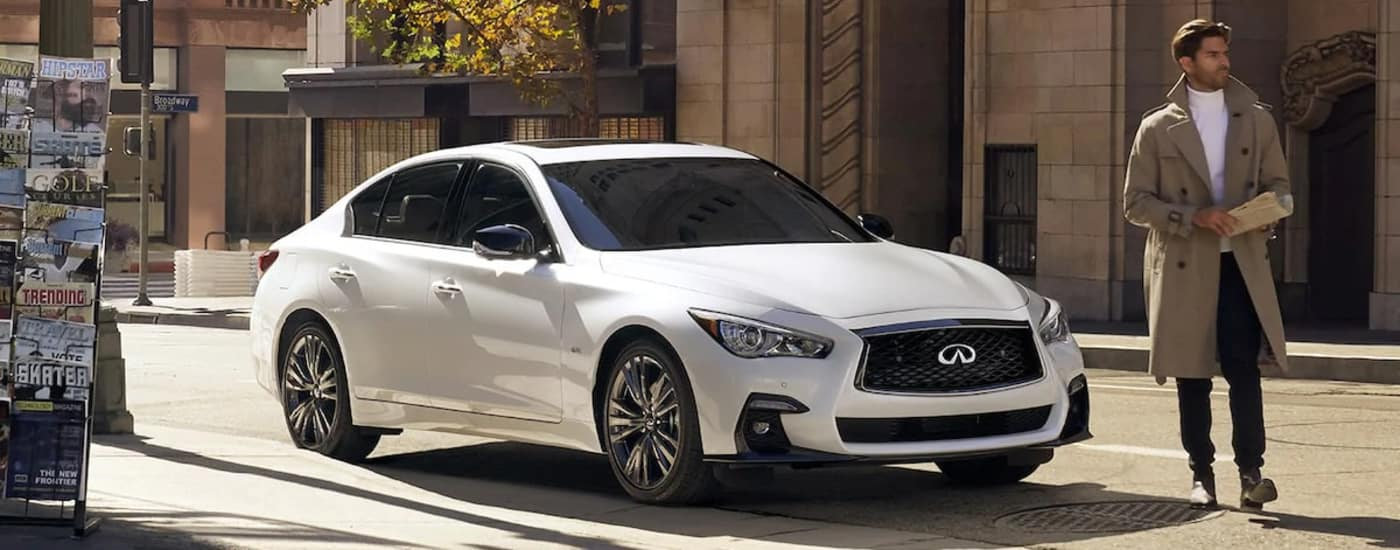 Man standing by Q50 on street