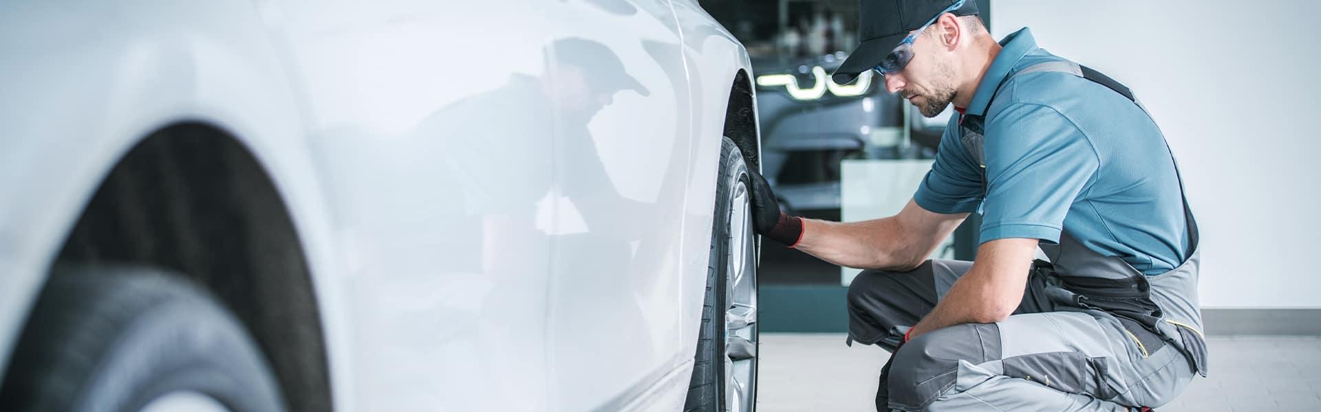 Bennett INFINITI of Wilkes-Barre is a Car Dealership near Scranton PA | Service Advisor Changing Tire on Vehicle