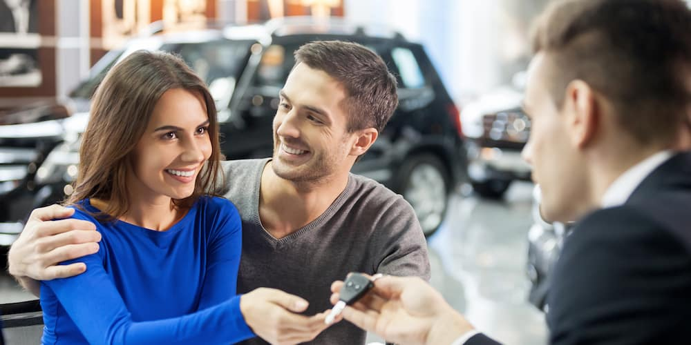 Young Couple Getting Keys to New Car