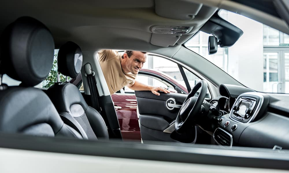 Man Inspecting Interior of Car