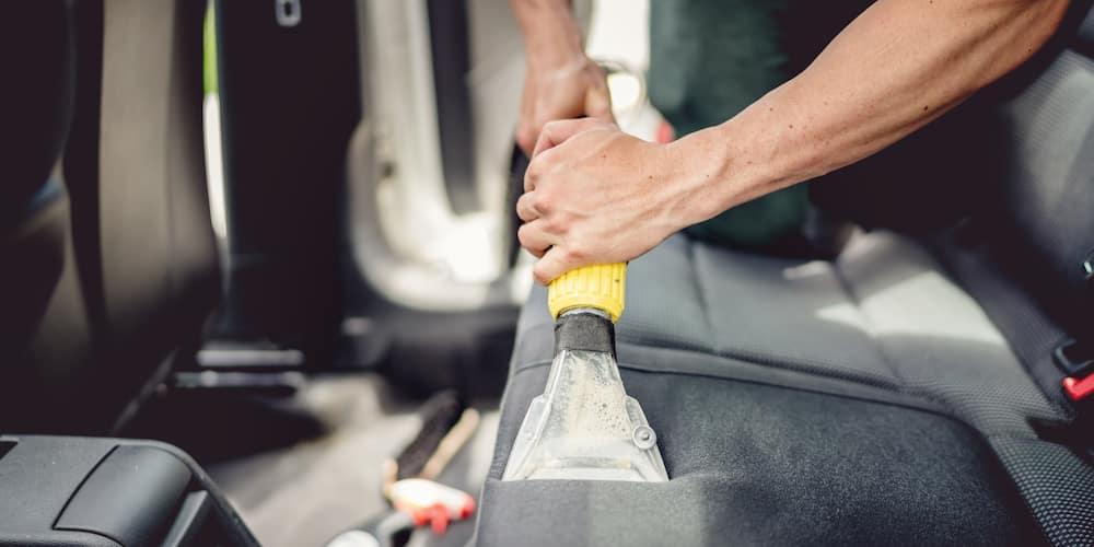 Man Vacuuming Cloth Car Seat