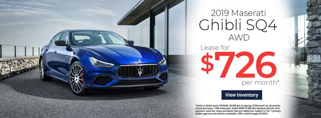 2019 Maserati Bhibli parked next to a building with all windows and steal and stone fence in the background