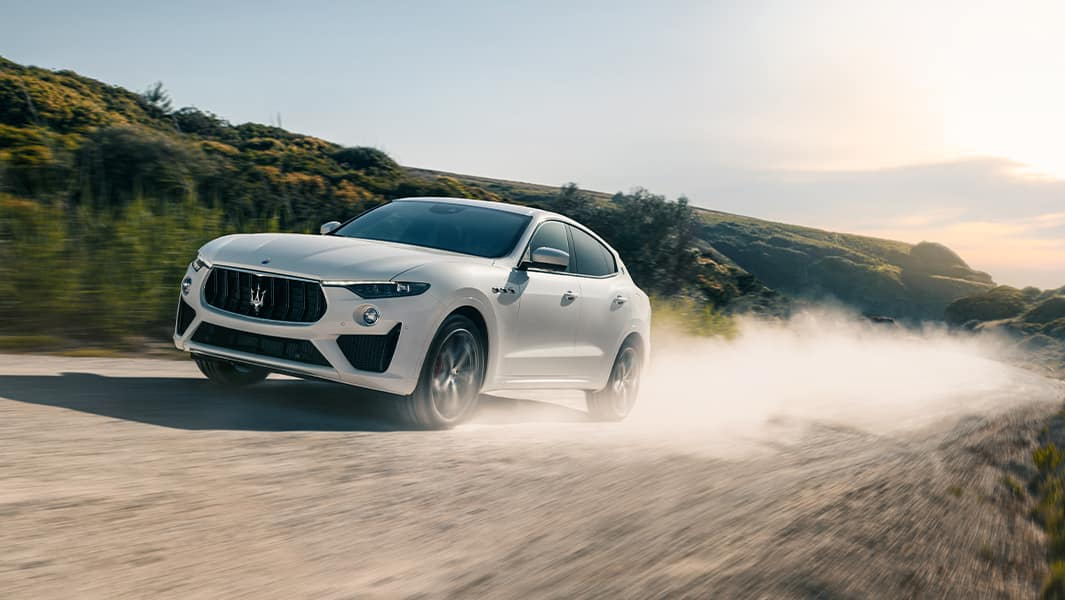 Bennett Maserati of Allentown is a Car Dealership near Bethlehem PA | White 2020 Maserati Levante Driving Fast Through Countryside Leaving Cloud of Dust Behind It