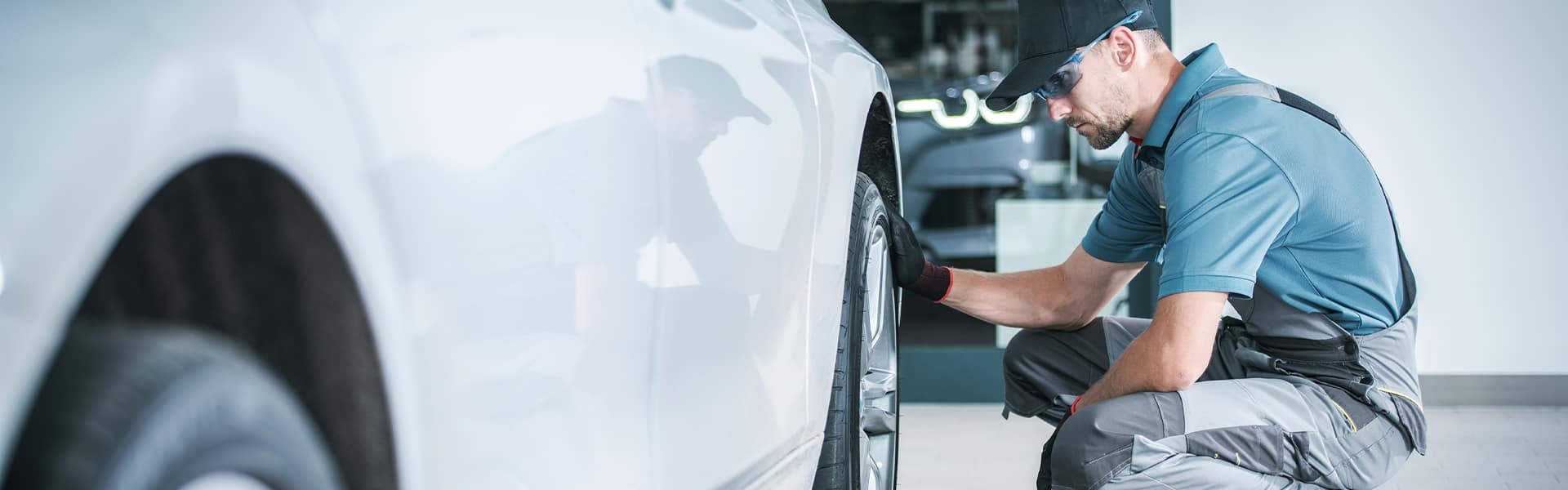 Bennett Maserati of Allentown is a Car Dealership near Bethlehem PA | Service Advisor Replacing Tire on White Sedan