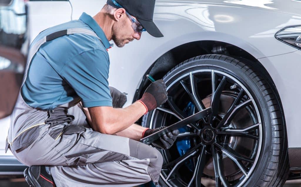 Bennett Maserati of Allentown is a Car Dealership in Allentown   Service Advisor inspecting tire on white sedan