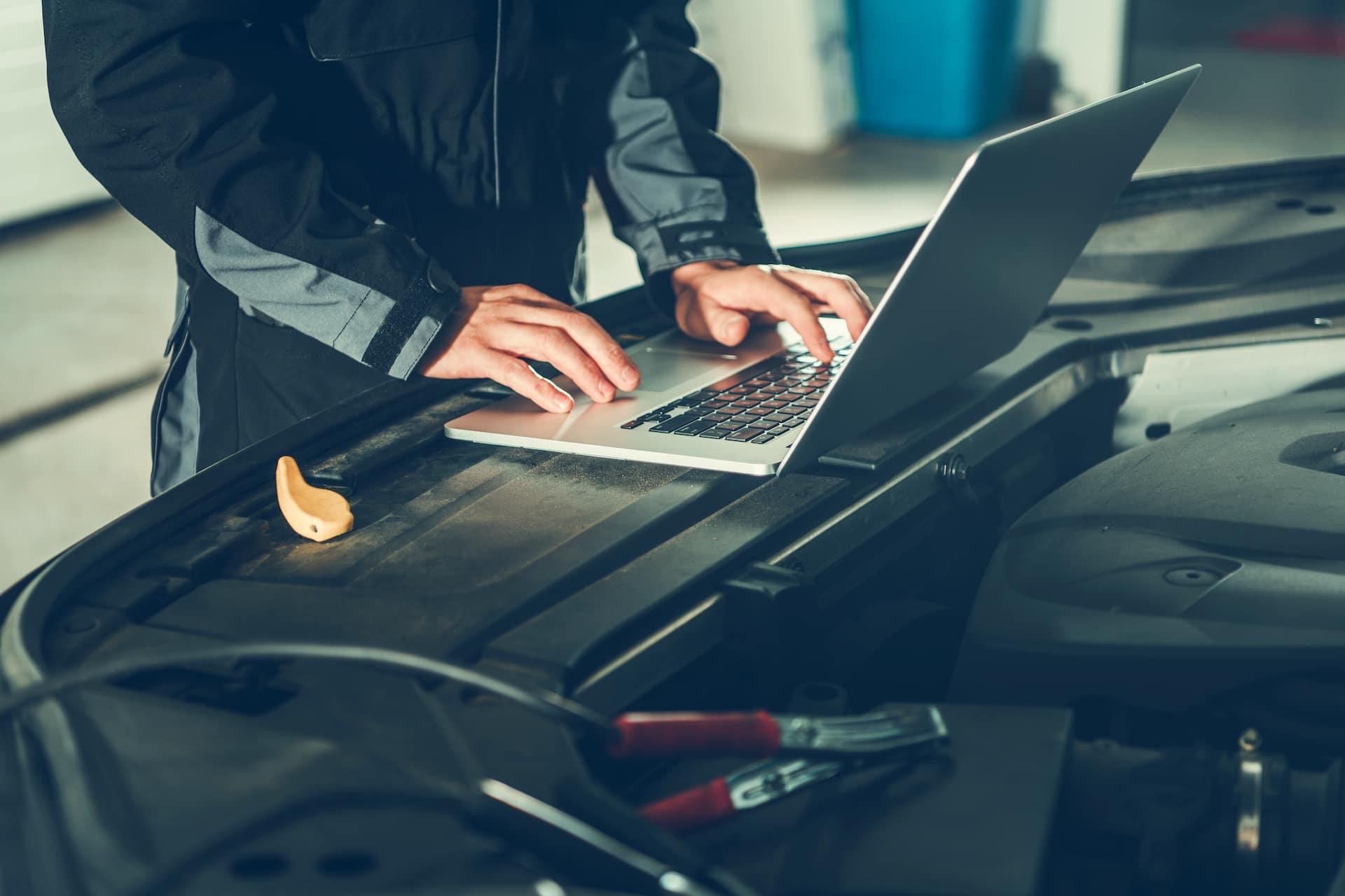 Mechanic typing on laptop | Bennett Maserati of Allentown is a Car Dealership near East Stroudsburg PA in Allentown