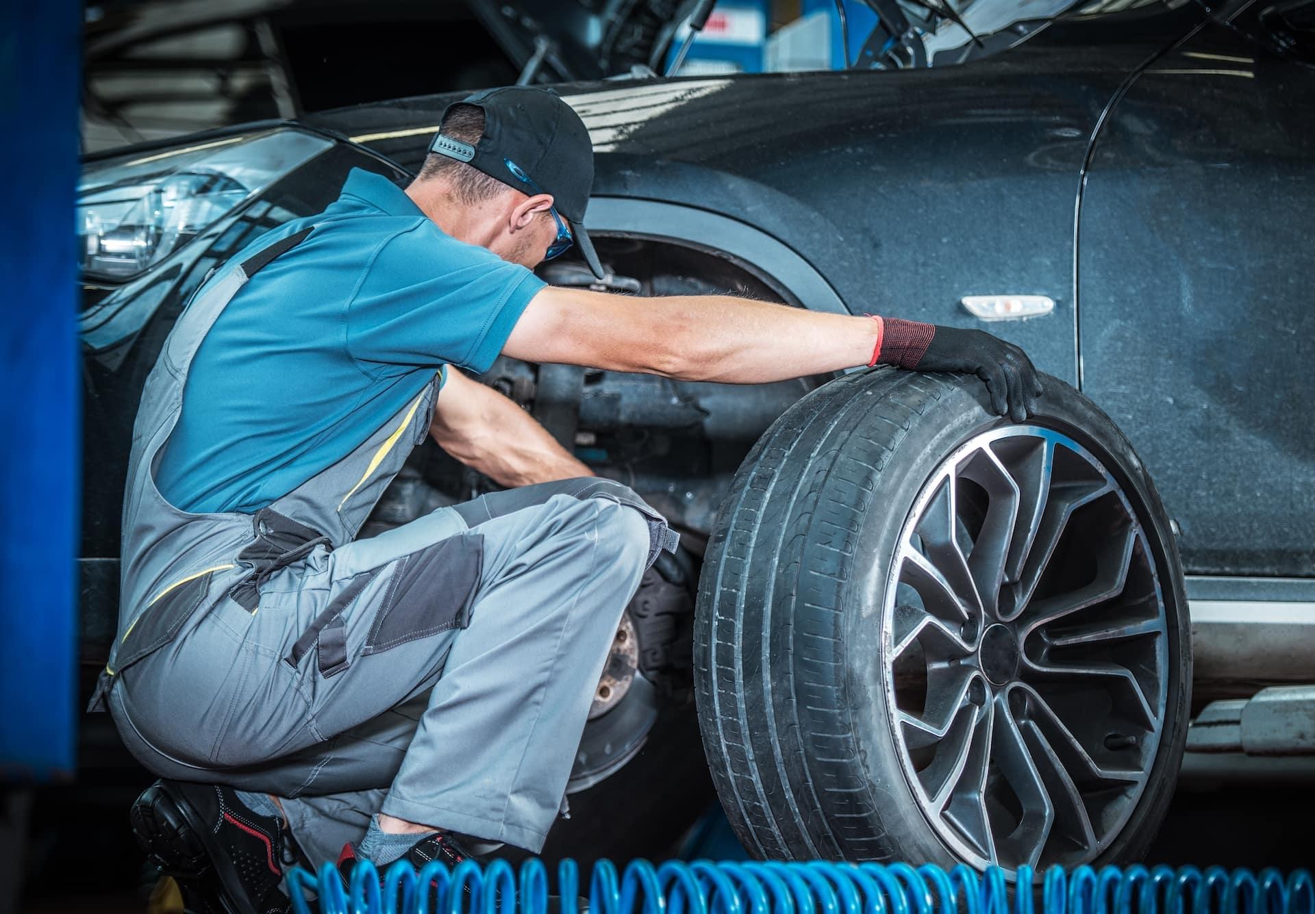Mechanic replacing tire | Bennett Maserati of Allentown is a Car Dealership near East Stroudsburg PA in Allentown