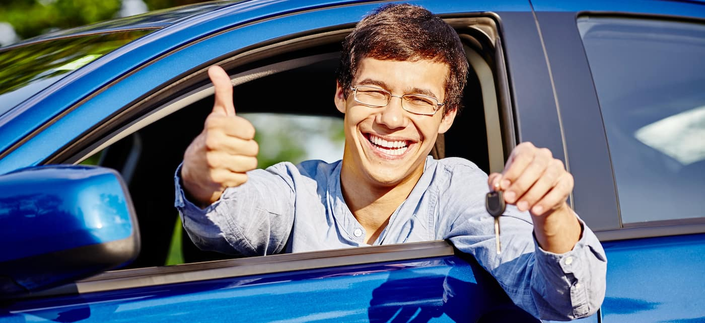 Close up of young man smiling holding car keys, giving a thumbs up sign out a car window