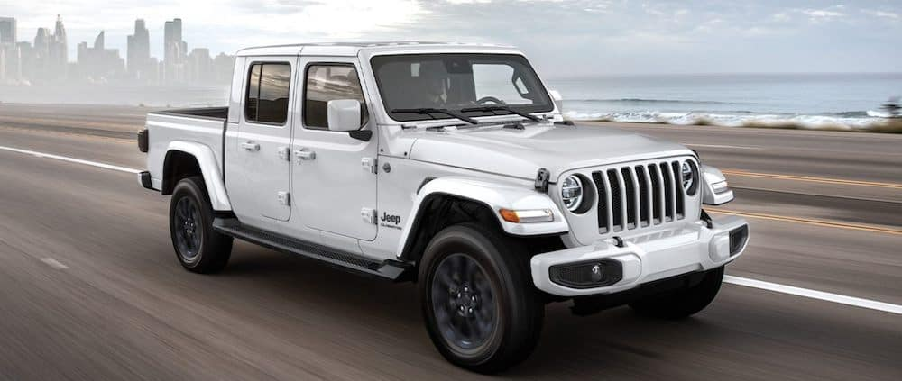 A 2020 Jeep Gladiator driving on a highway on the coast