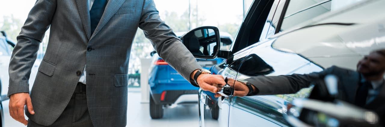 man holds car door handle
