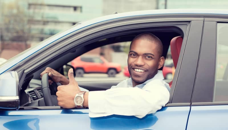 man showing thumbs up in new blue car
