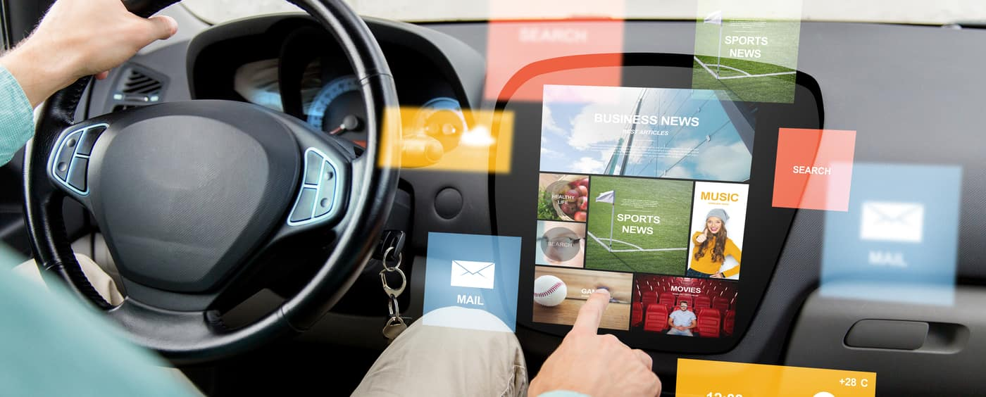 man driving car with news on board computer