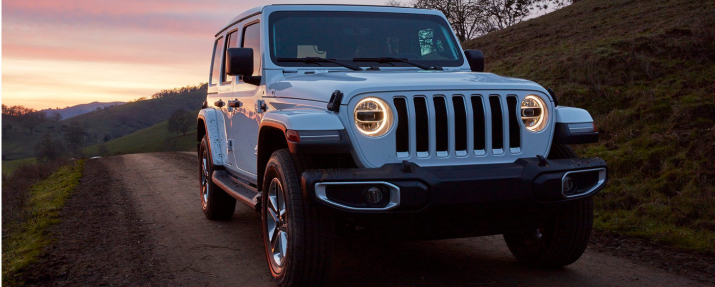 White Jeep Wrangler with their headlights on