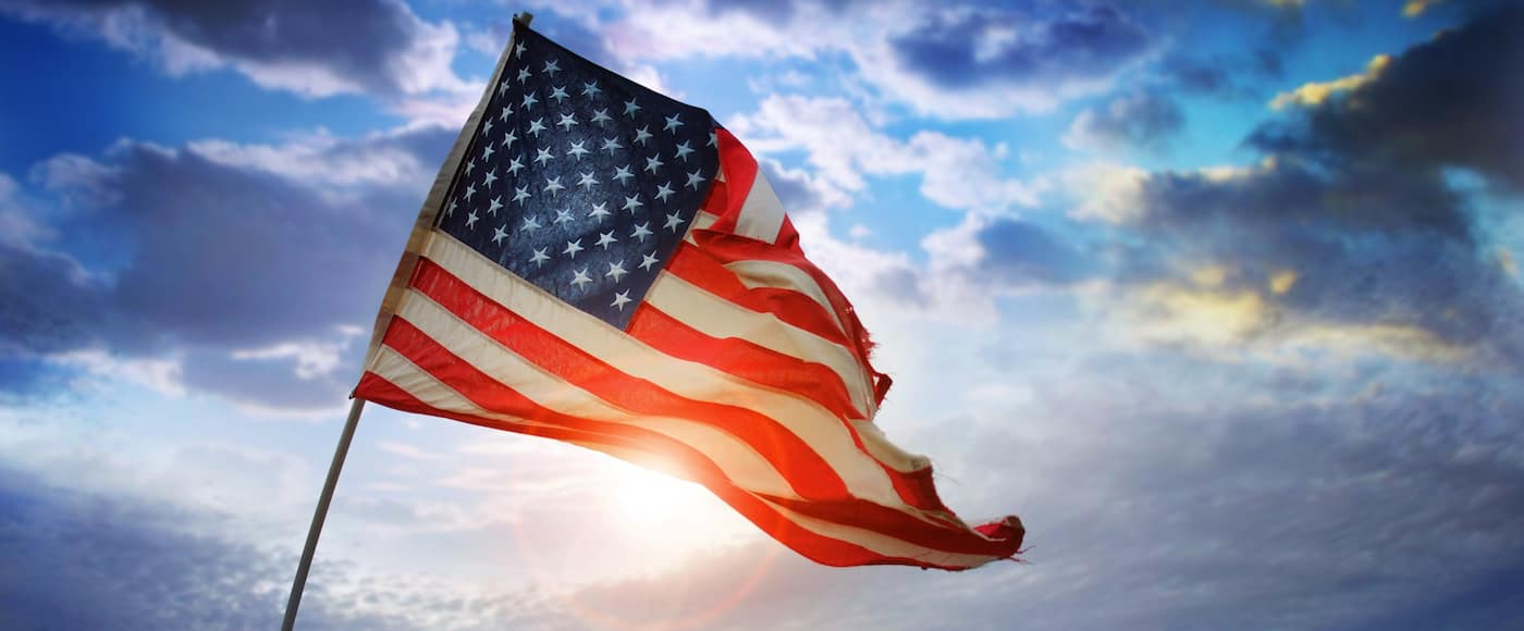 American flag waving in front of the sky