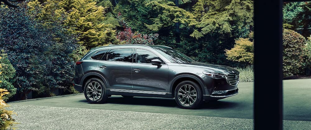 A 2020 Mazda CX-9 parked in a driveway surrounded by trees