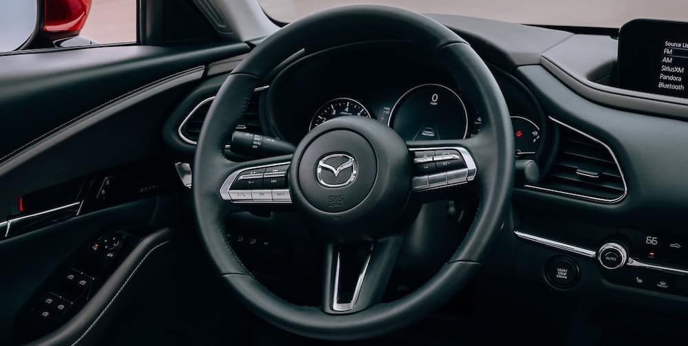 The steering wheel and dash panel inside the 2020 Mazda CX-30