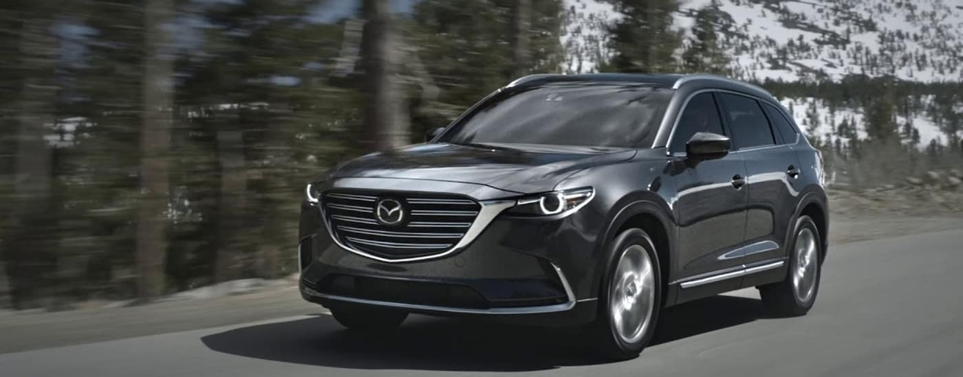 2020 Mazda CX-9 driving down road by a mountain