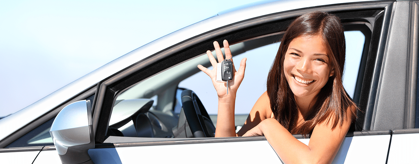 Woman holding keys sitting in her new car