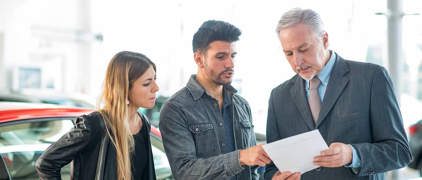 Couple Talking to Car Salesman Looking a Piece of Paper