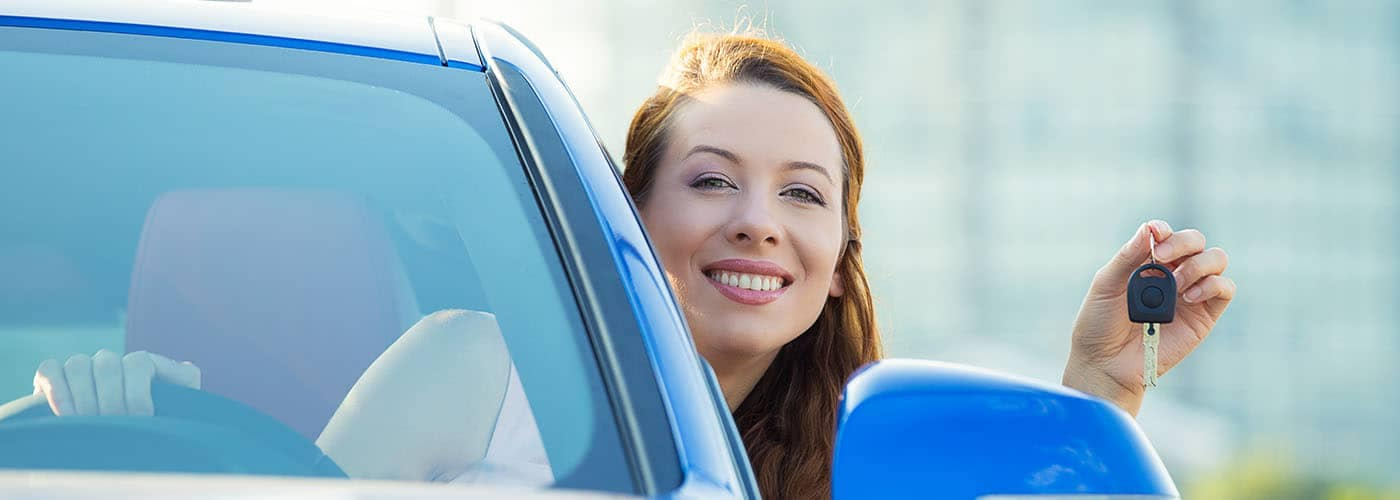 Happy Woman holding Car Keys out Window