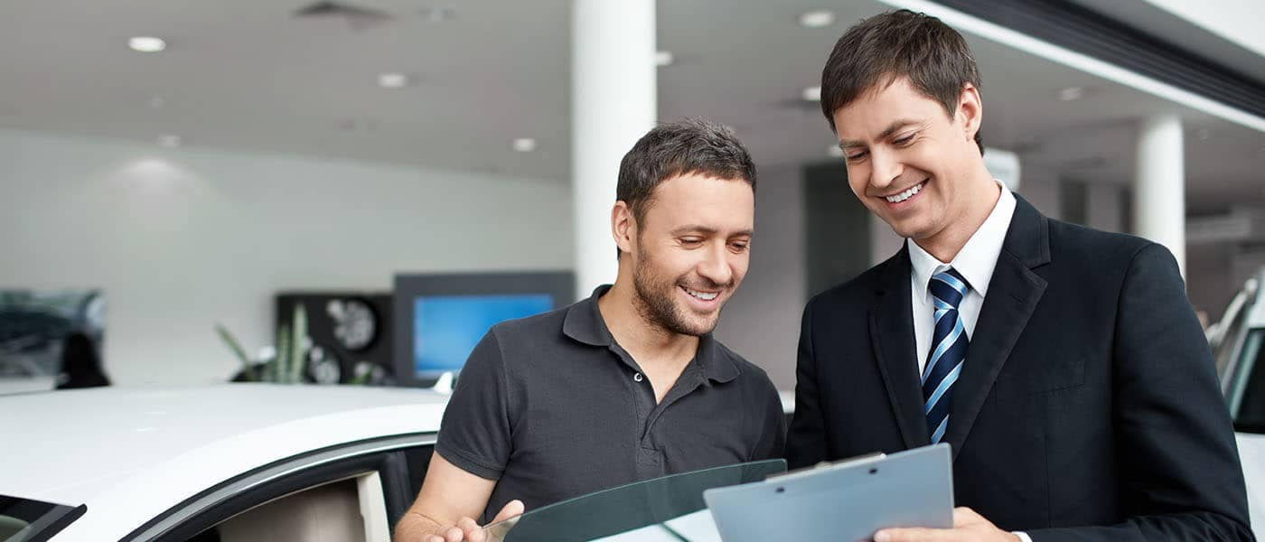Man smiling while salesman showing him papers