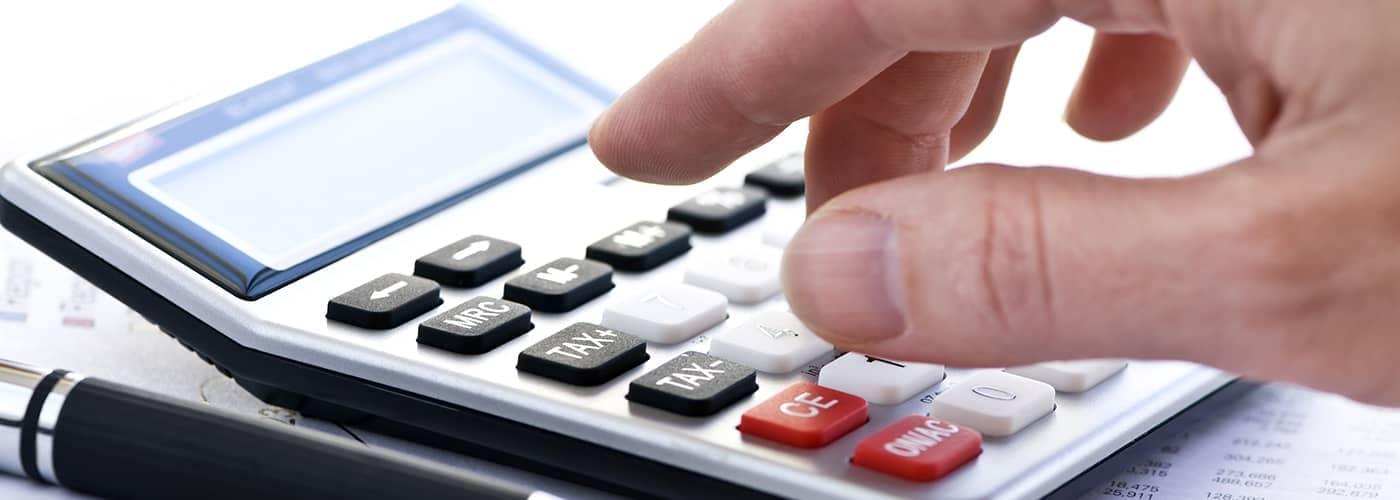 Man typing on calculator
