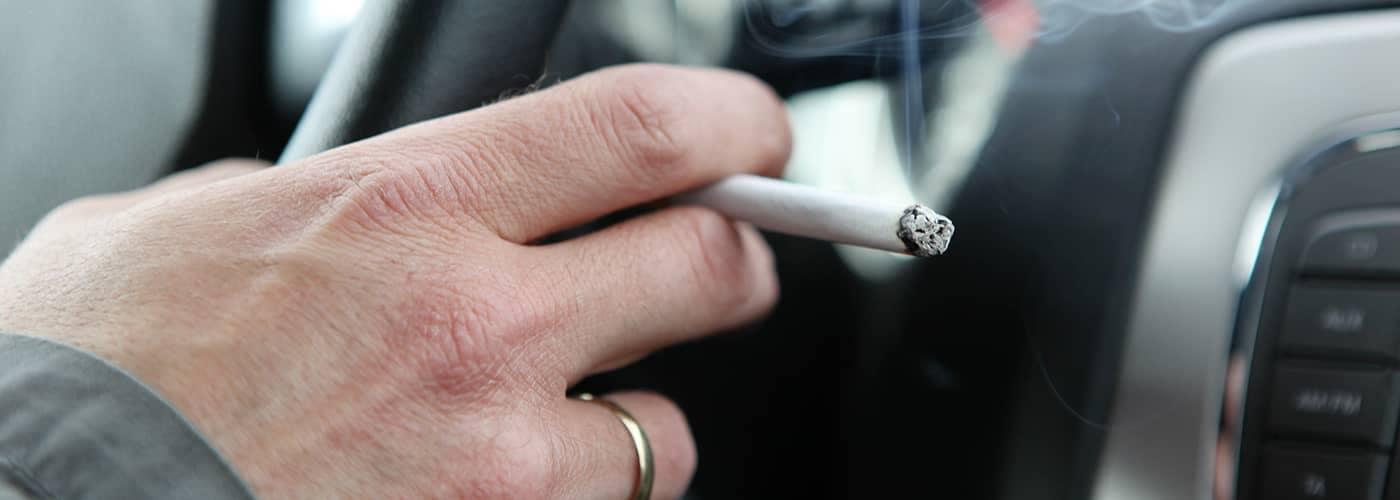 Man smoking cigarette in car