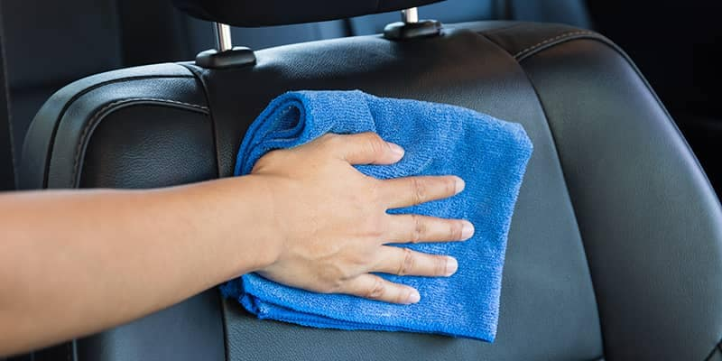 Closeup of person wiping down leather seats