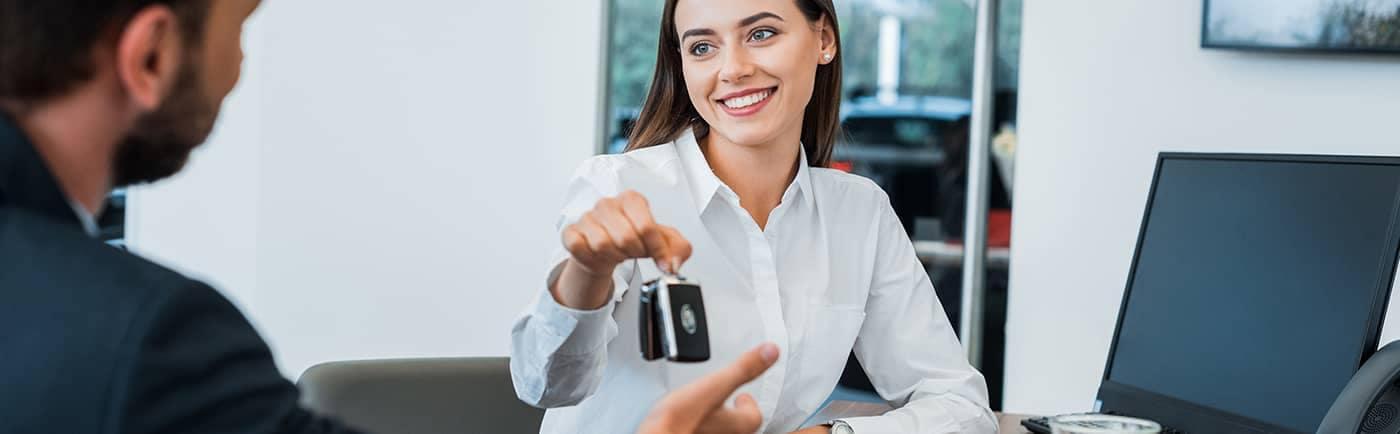 Sales Woman Handing Man Car Keys