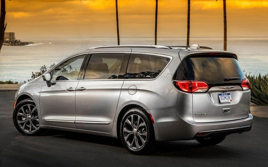 Image of a silver 2019 Chrysler Pacifica parked near the ocean at sunset.