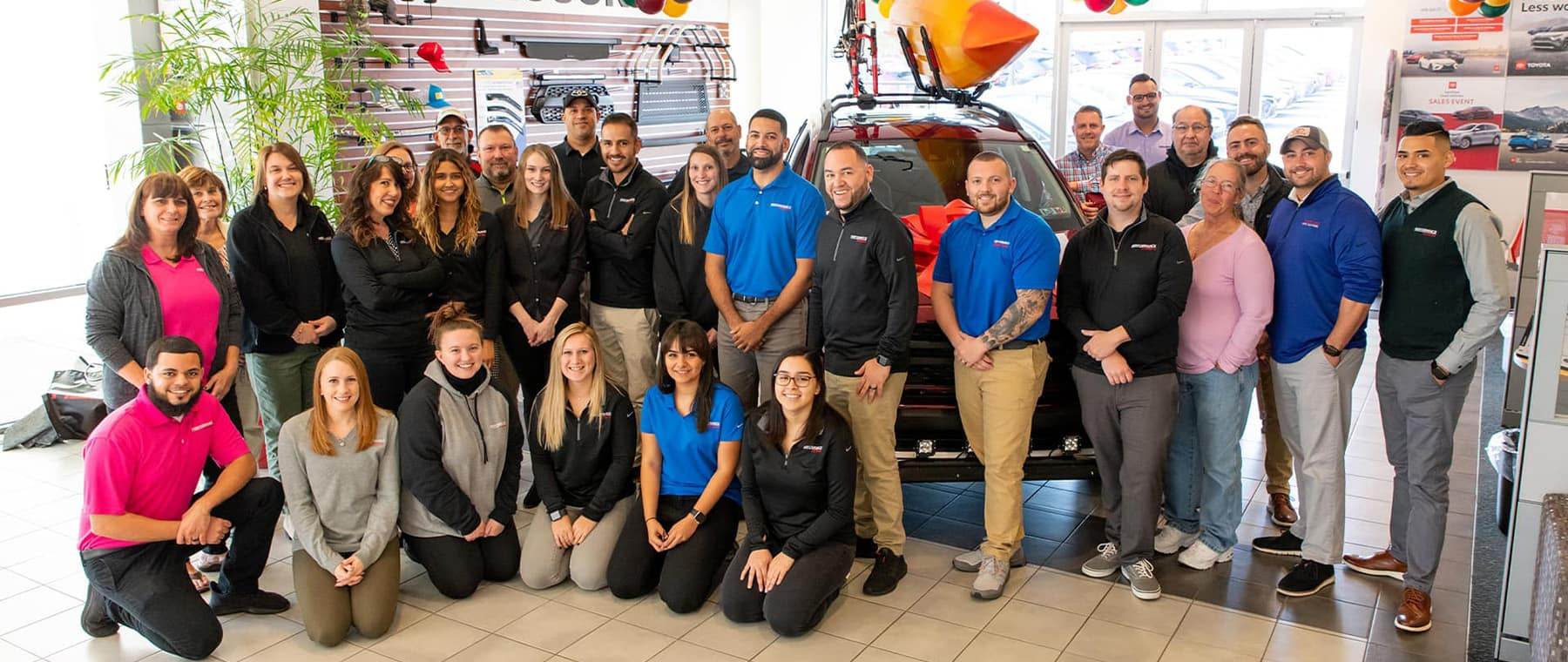 staff members standing taking picture at Toyota car dealership