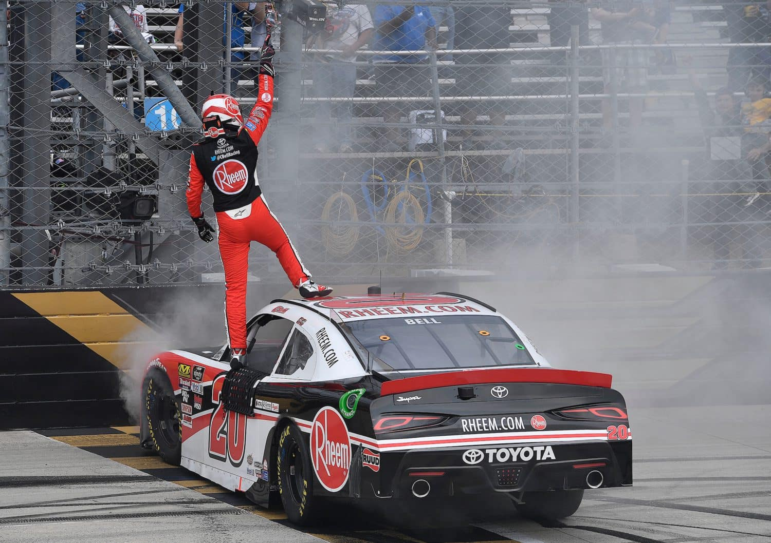 Christopher Bell stands victorious following NASCAR race.