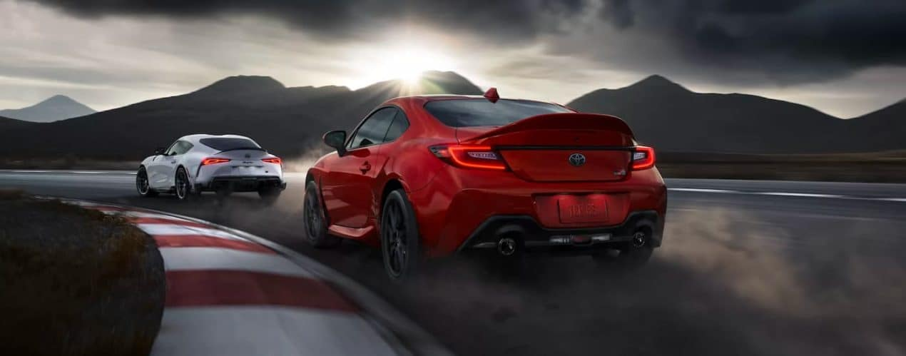 A red 2022 Toyota GR 86 is shown from the rear following a 2022 Toyota GR Supra A91 CF Edition around a wet track.