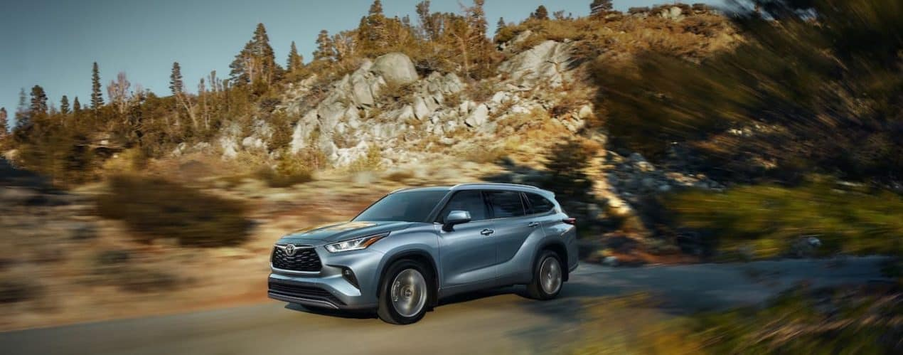 A blue 2021 Toyota Highlander Platinum is shown driving past a hill.