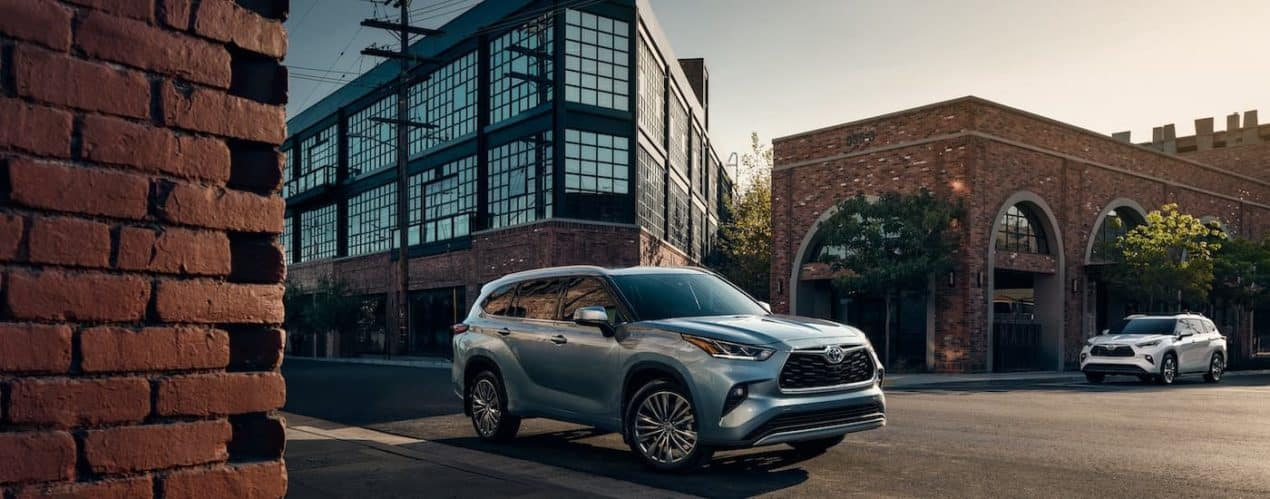 A blue 2021 Toyota Highlander Platinum and a silver XLE are shown parked in the city.