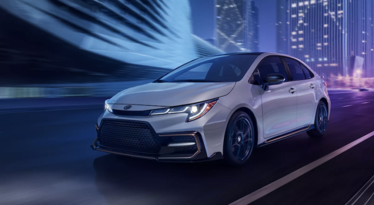 A white 2022 Toyota Corolla is shown driving through a city at night.