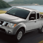2019 Nissan Frontier towing a trailer with car on rural highway