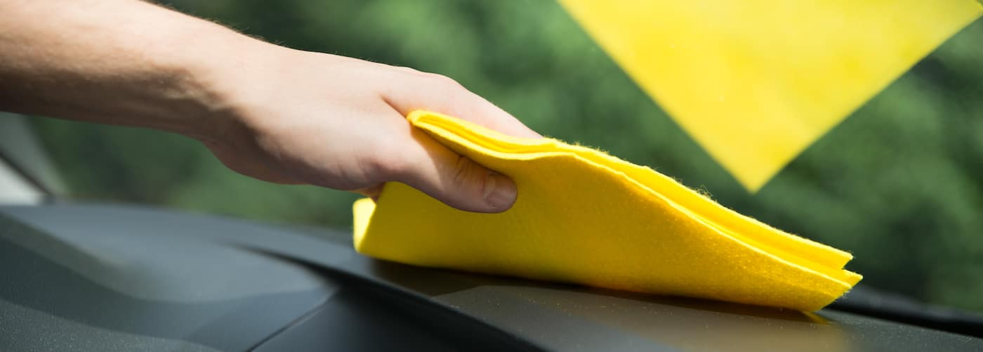 close up of hand cleaning interior windshield with fabric cloth