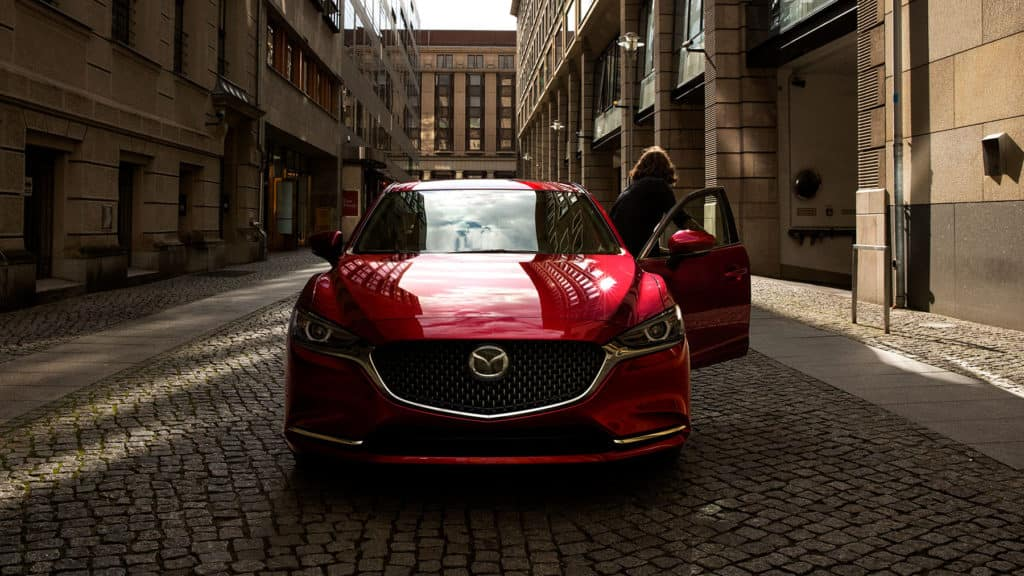 Image of a red 2019 Mazda6 parked on a street.
